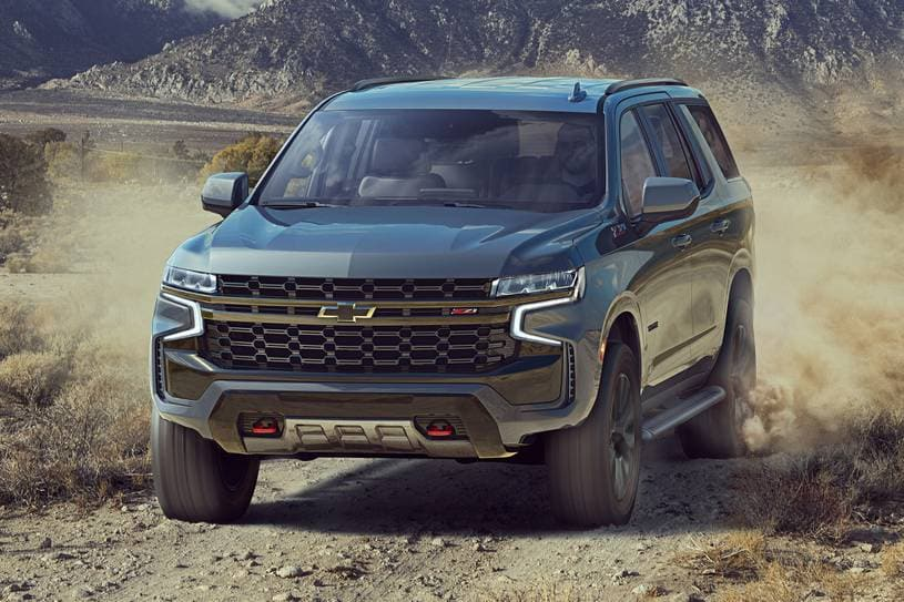 A light colored 2021 Chevy Tahoe Z71 off-roading on a dirt covered road in the mountains