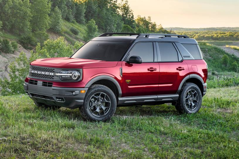 A red 2021 Ford Bronco Sport parked in a field filled with green grass