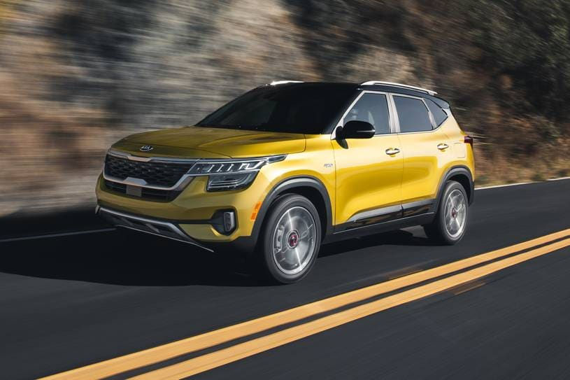 A yellow 2021 Kia Seltos driving quickly down the road