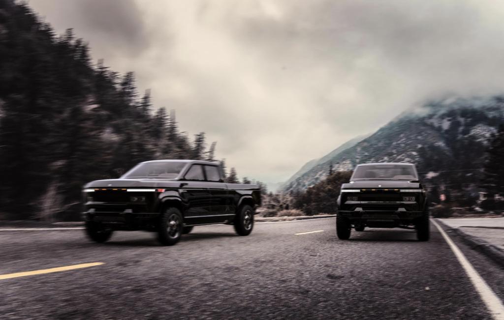 A pair of 2022 Atlis XT pickup trucks driving down a mountain road