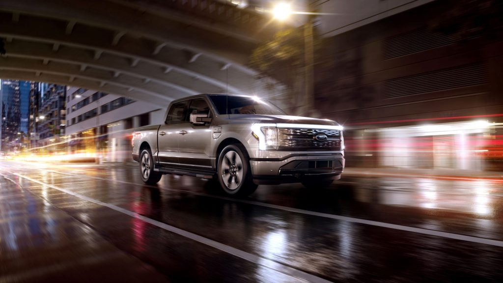 A silver 2022 Ford F-150 Lightning Platinum drives through a rain-soaked city at night