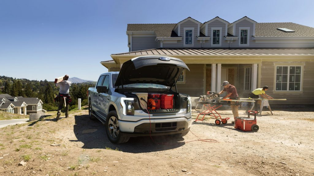 Workers at a home construction site run power tools and store items in a silver 2022 Ford F-150 Lightning XLT
