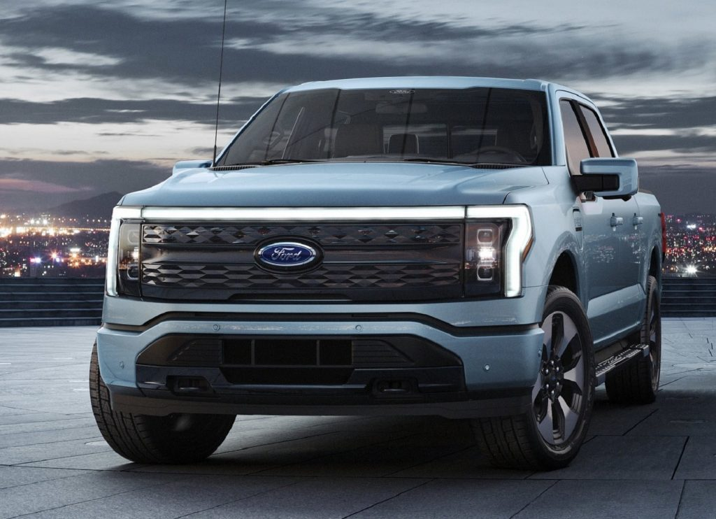 The front 3/4 view of a light-blue 2022 Ford F-150 Lightning on a parking-garage roof in a city