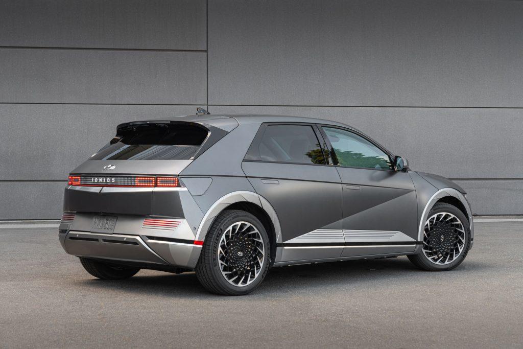 The rear 3/4 view of a gray-silver 2022 Hyundai Ioniq 5 by a gray building