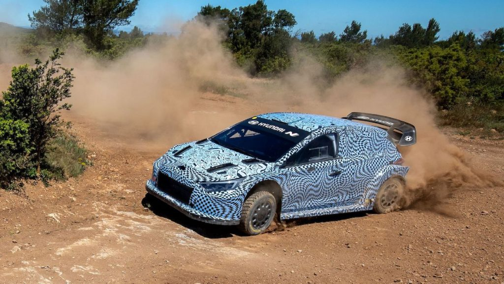 The side view of the blue-and-white-camouflaged 2022 Hyundai i20 N Rally1 prototype drifting on a gravel rally stage