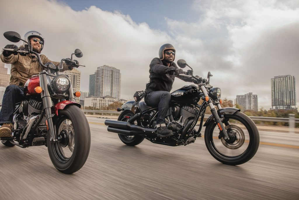 A black and a red 2022 Indian Chief riding down a damp city highway