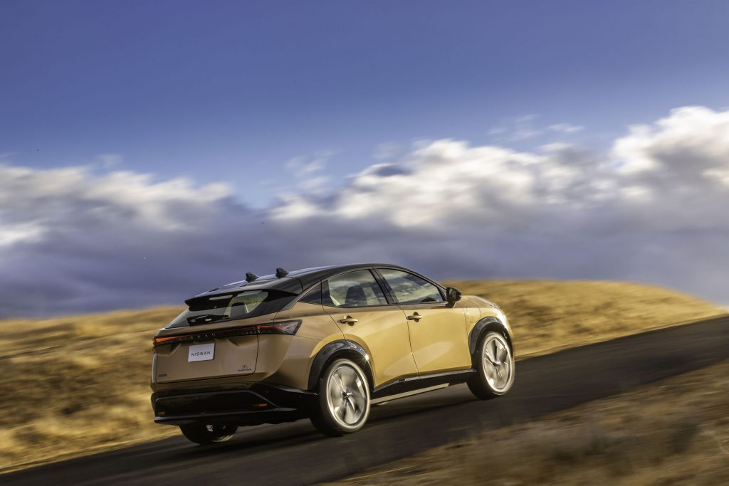A gold 2022 Nissa Ariya electric compact SUV traveling uphill on a partly sunny day
