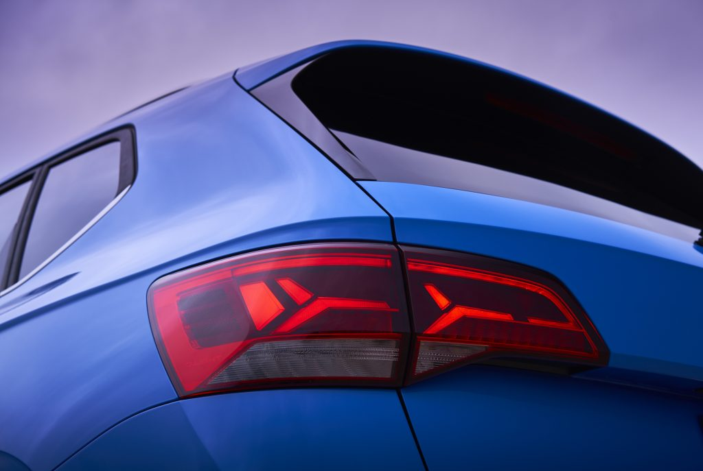 A rear driver's side view of a blue 2022 Volkswagen Taos SUV's taillight and back window
