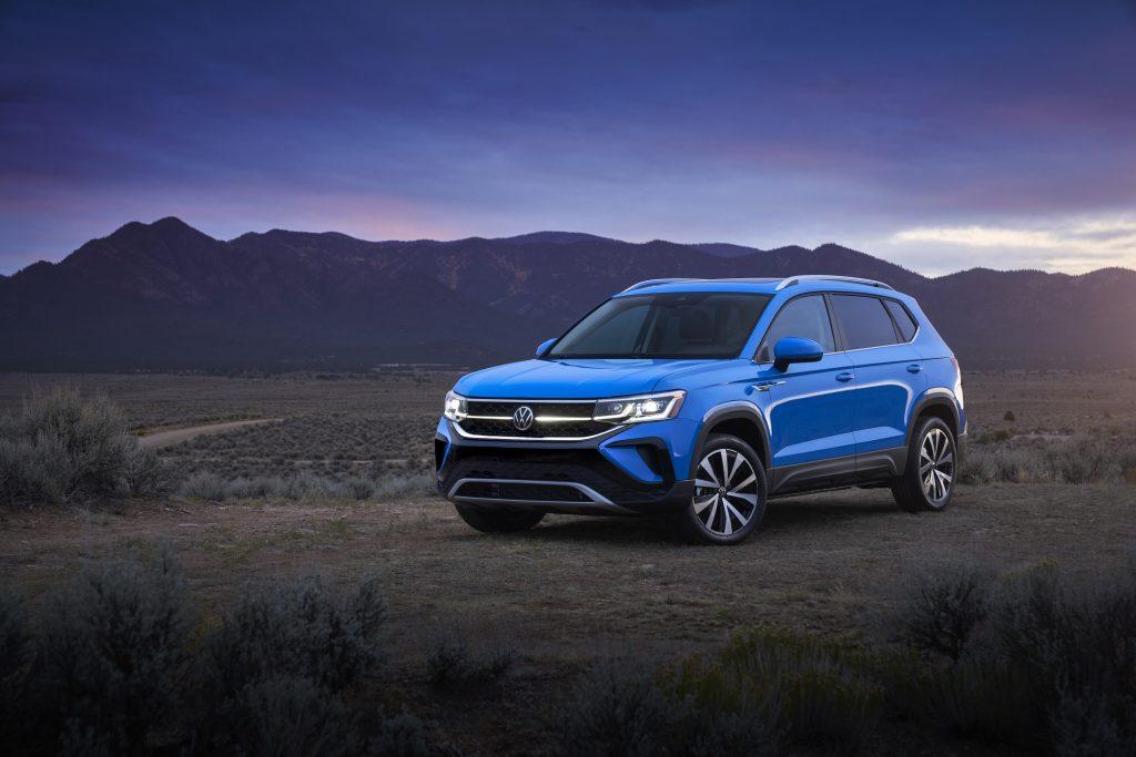 The 2022 VW Taos in blue driving in the desert near dusk.