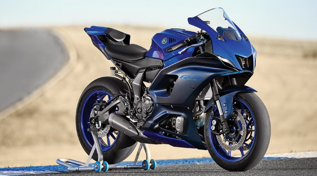 A blue-and-black 2022 Yamaha YZF-R7 on a rear-wheel stand on a desert racetrack