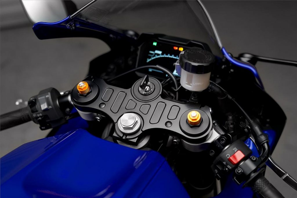 The clip-on bars and LCD dash of a blue 2022 Yamaha YZF-R7