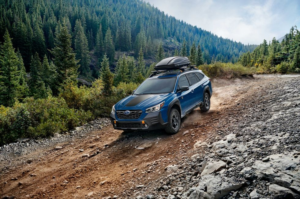 A blue 2022 Subaru Outback Wilderness driving down a dirt road near the forest