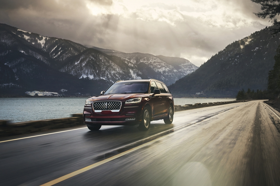 The 2021 Lincoln Aviator PHEV driving down a road near water and mountains