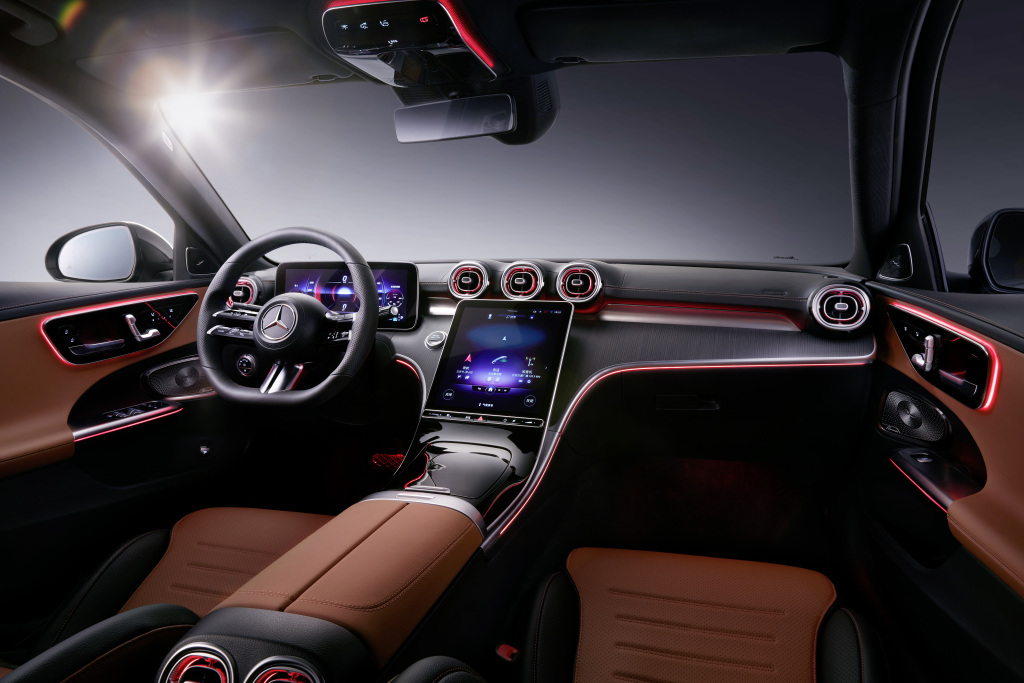 The interior of the Mercedes C-Class, with a large touch screen in the center and coffee-colored seats
