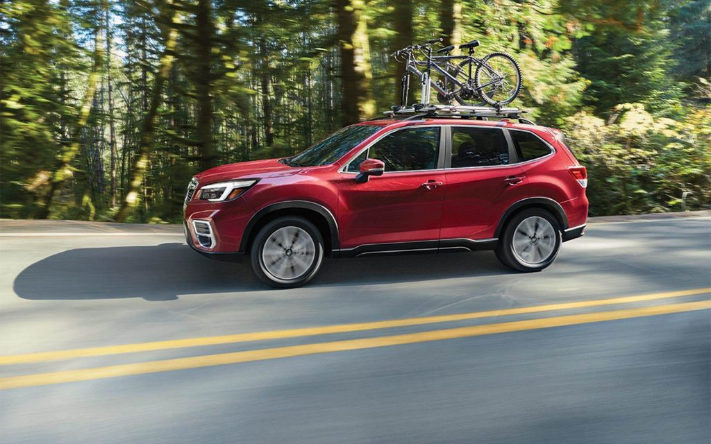 a red 2021 Subaru Forester crossover SUV driving on a scenic wooded road