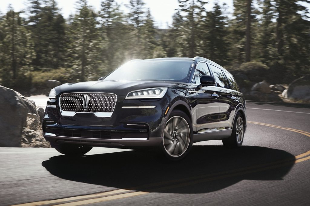The 2021 Lincoln Aviator driving on a curvy road through the forest