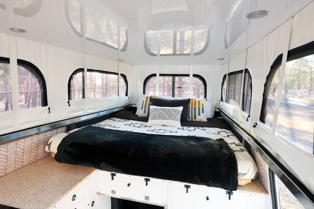 an inviting bed in EarthCruiser's new picturesque 4x4 overland chalet interior