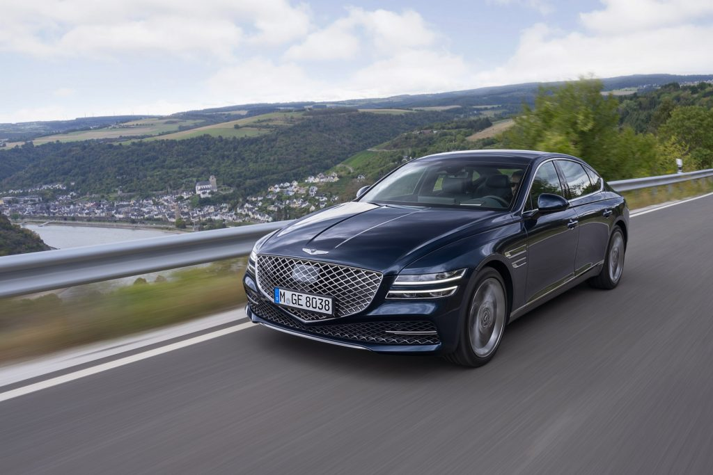 A blue Genesis GV80 sedan drives down a mountain road shot from front 3/4