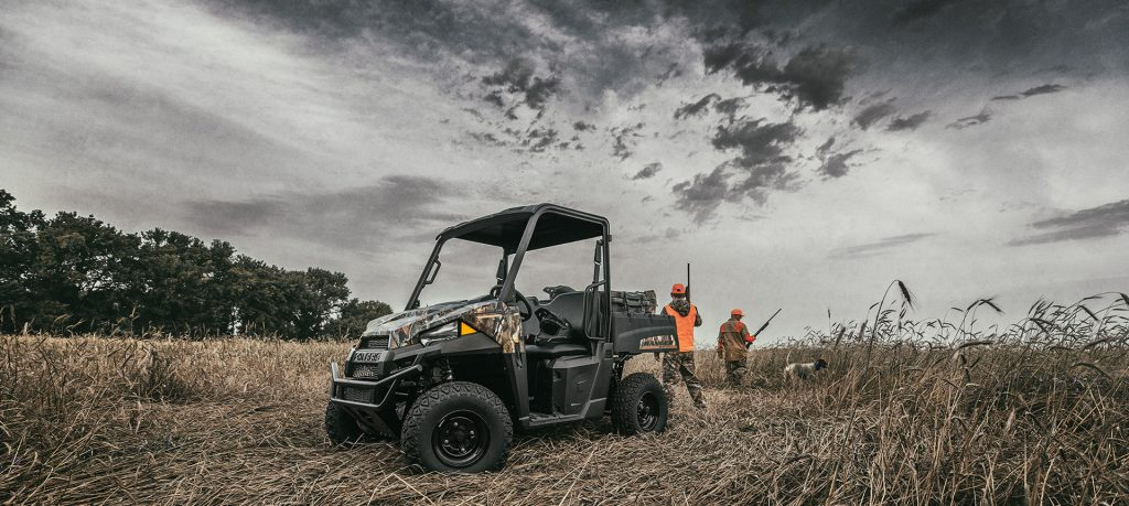People in orange vests hunting in a field with a dog and the Polaris Ranger EV