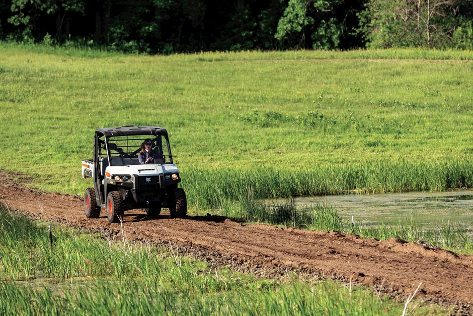 a bobcat utility vehicle driving through farmland on a dirt road