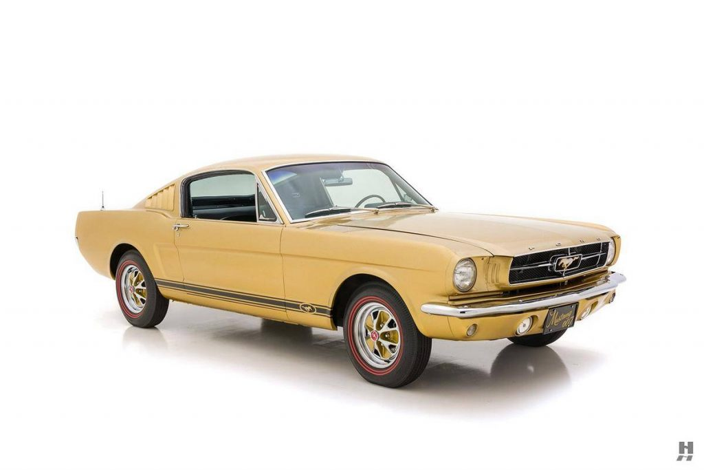 An image of a gold Ford Mustang parked inside of a photo studio.