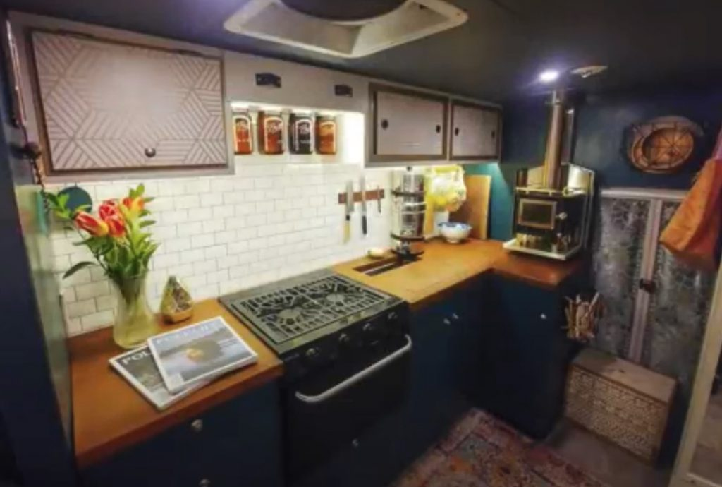 the interior of the camper van with a view of the functional full kitchen