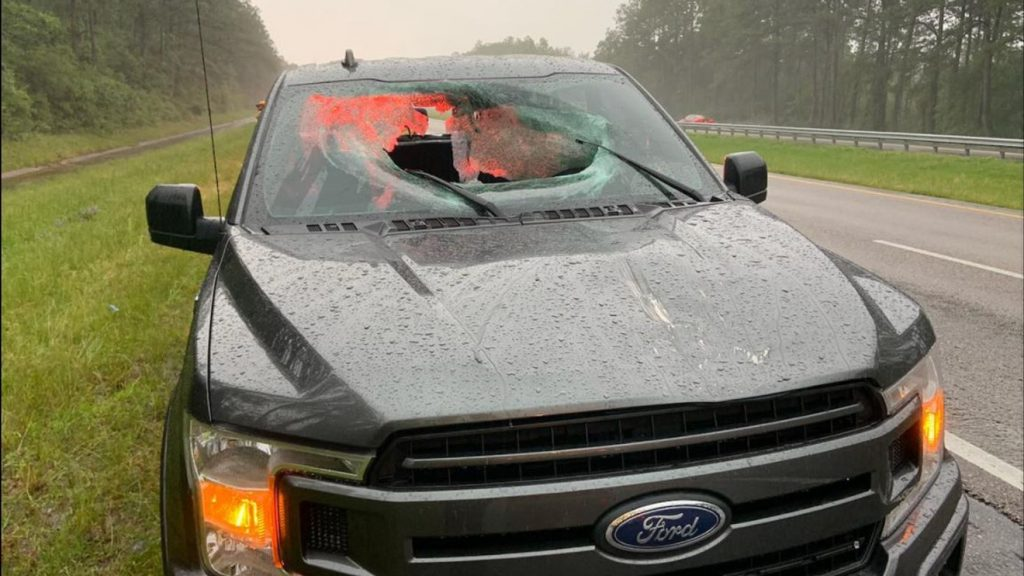 A Ford F-150 with a broken windshield by the side of the highway in Florida