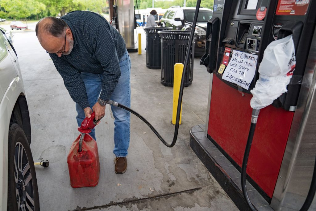 A motorist fills a red plastic gas can at an Atlanta, Georgia gas station