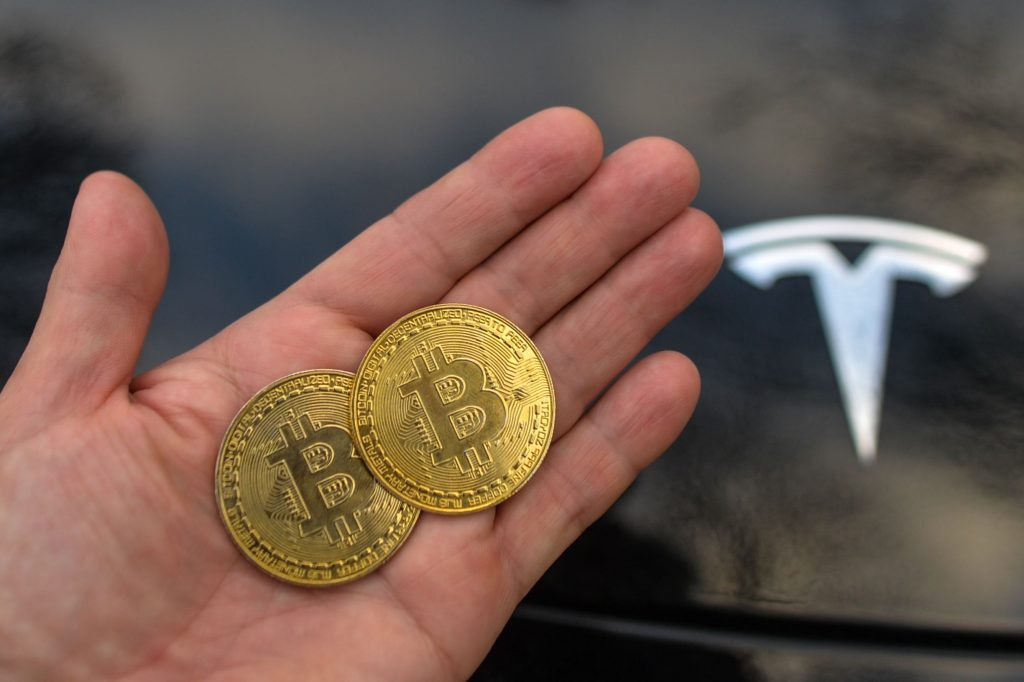 A person holds two commemorative Bitcoin coins next to a black Tesla EV