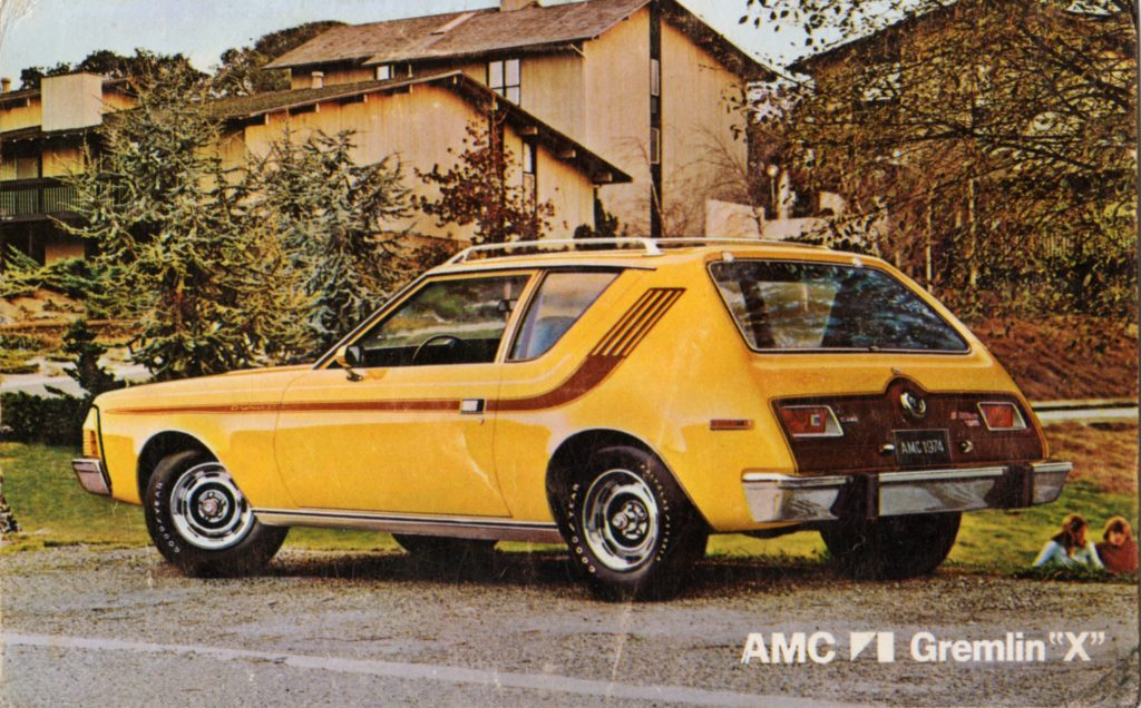 A yellow AMC Gremlin is parked in a 70s suburban neighborhood and ranks in many most hated cars lists.