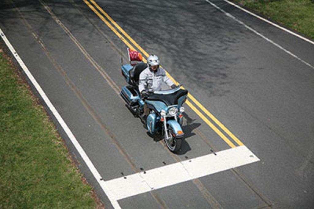 An FHWA engineer tests induction-loop traffic light sensor sensitivity on a light-blue motorcycle