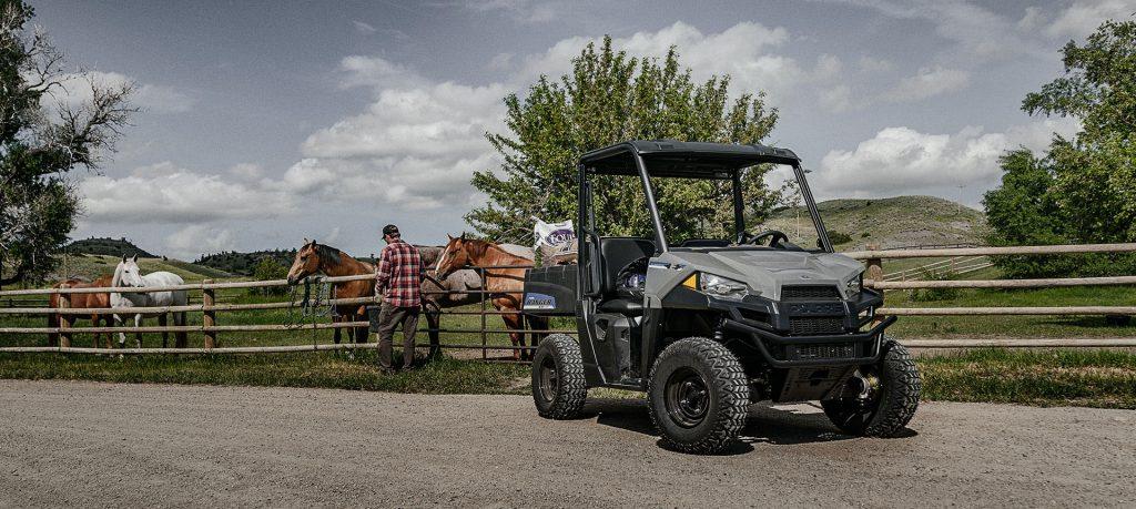 The Polaris Ranger EV parked near a corral of horses on a ranch