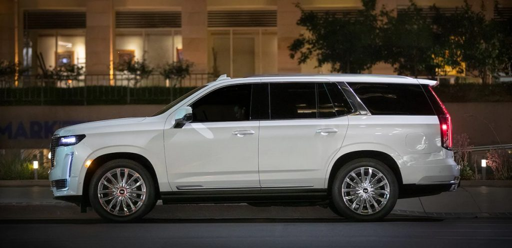 A luxurious white 2021 Cadillac Escalade is parked on a city street.