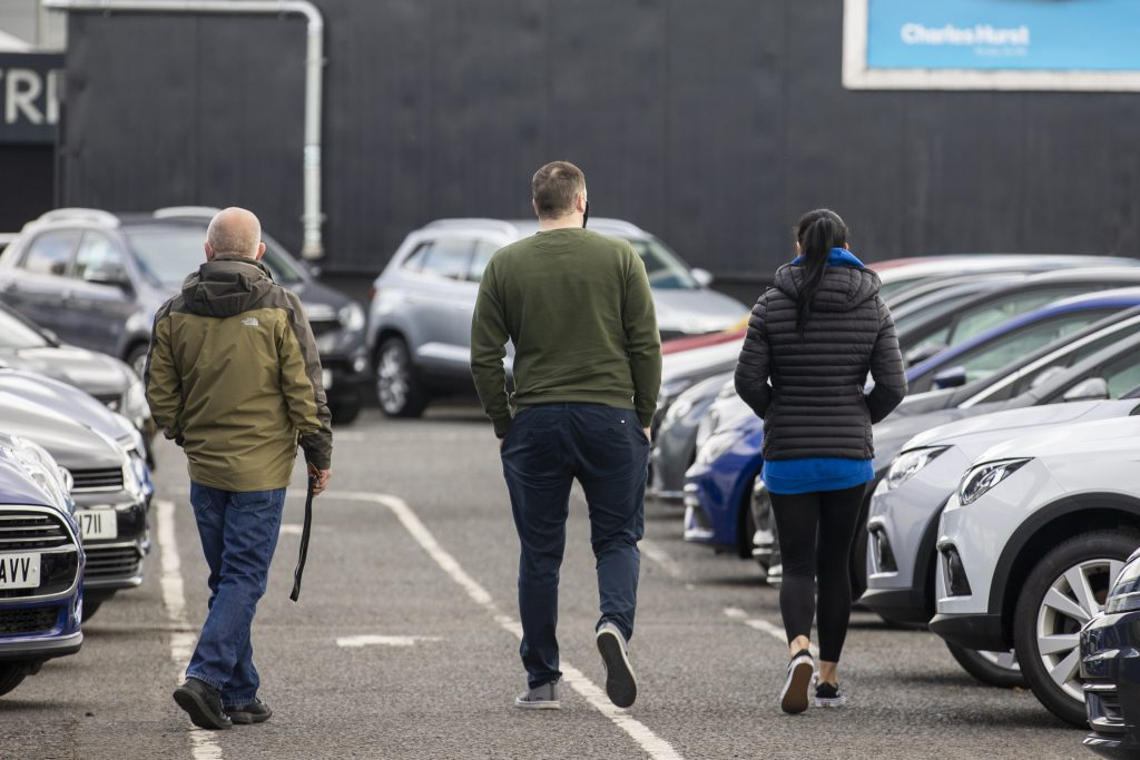 Potential car shoppers walk around Charles Hurst Usedirect used car dealership on Boucher Road