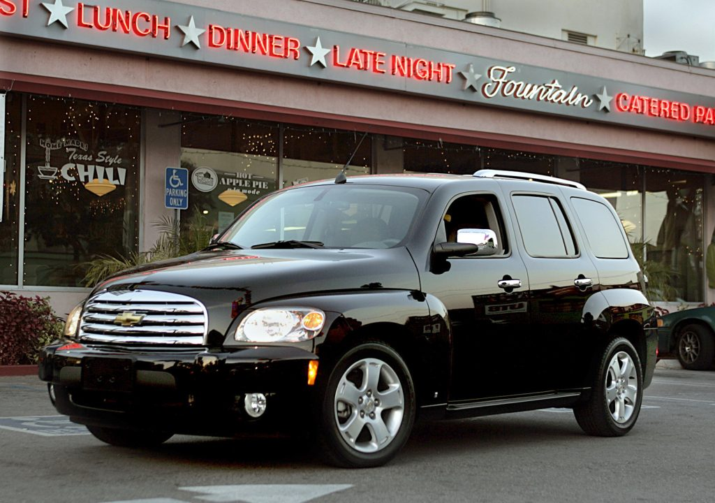 One of the best unpopular cars, the sleek black Chevy HHR is parked in front of a Hollywood diner.