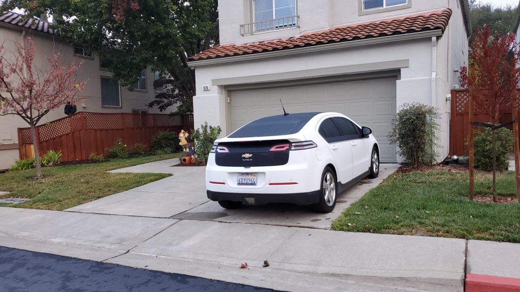 Chevrolet Volt electric car parked on the driveway of a suburban home.