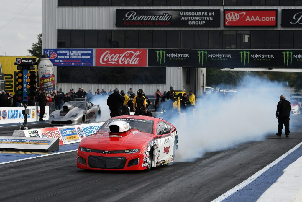 A Chevy does a burnout on a drag racing track.