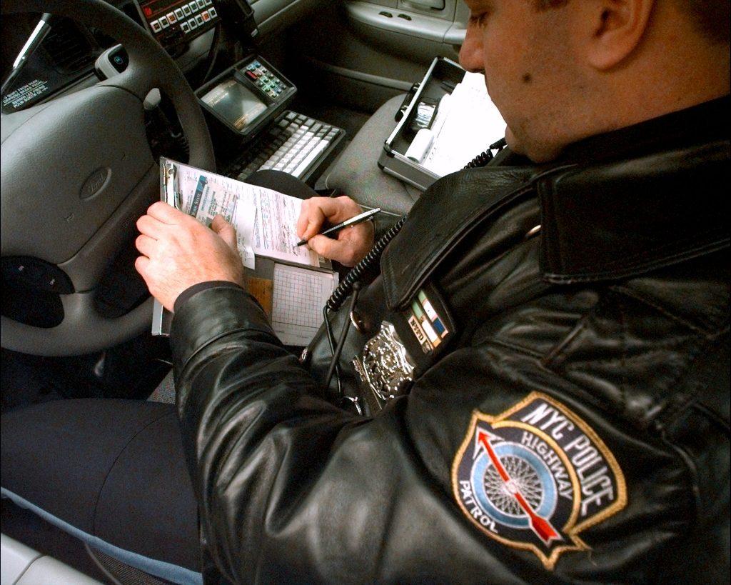 A police officer writes a speeding ticket after clocking cars with a radar gun.