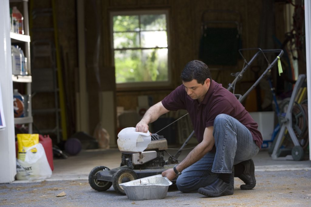 Man in the process of changing his lawnmower's oil outside a garage, using a disposable aluminum catch pan.