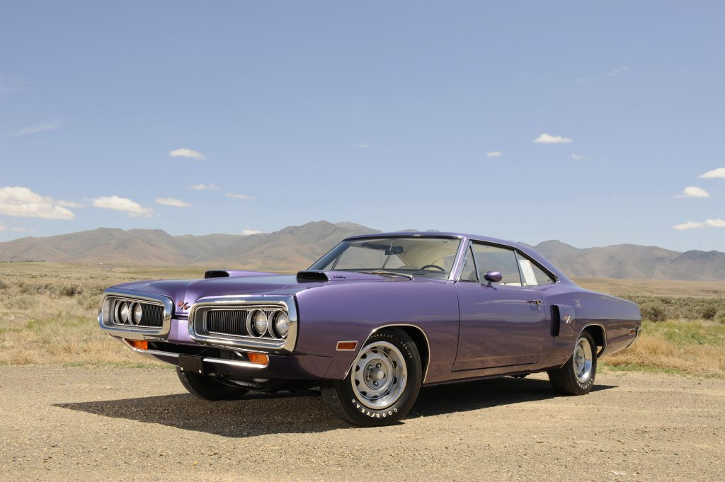 A 1970 purple Dodge Coronet Hemi RT sits on the dusty acrid planes, framed by mountains in the distance.