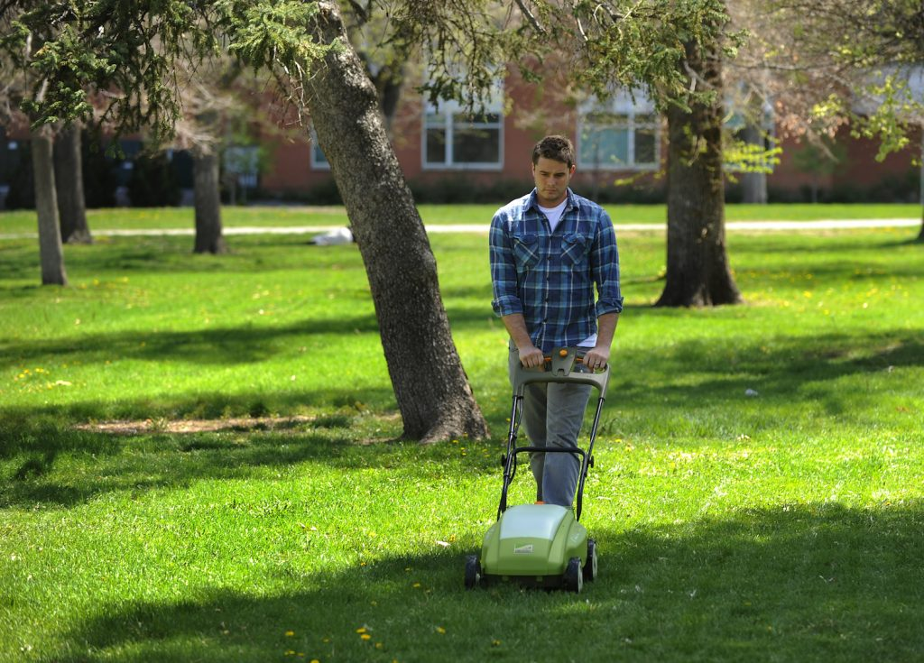 A young man demonstrating an electric lawn mower