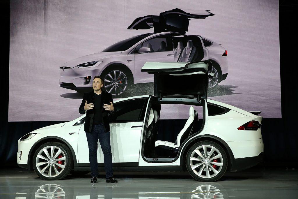 Tesla CEO Elon Musk stands outside of a Tesla Model X.