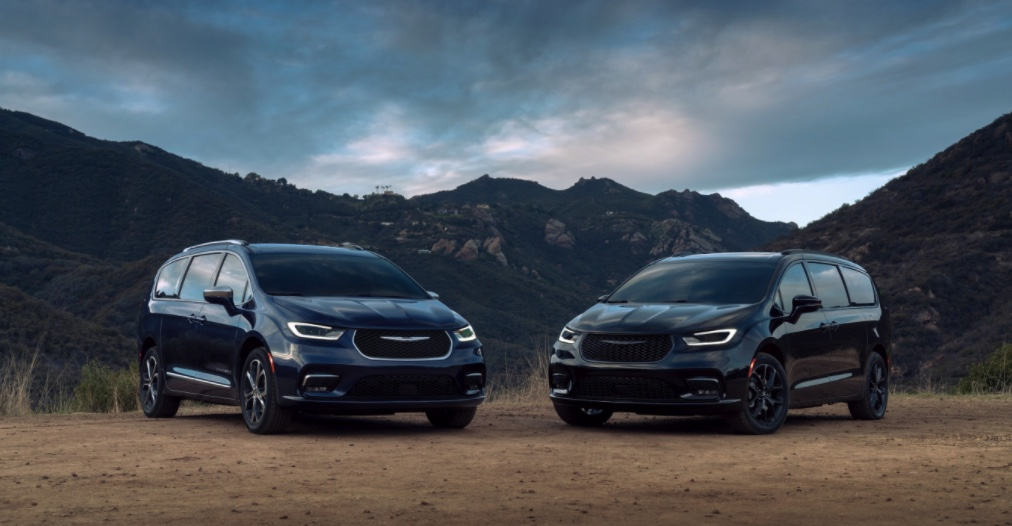 two 2021 Chrysler Pacifica models parked in the dirt in front of mountains