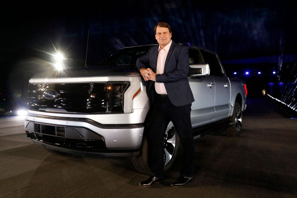 Ford Motor Company's chief executive officer Jim Farley poses next to the newly unveiled electric F-150 Lightning outside of their headquarters in Dearborn, Michigan