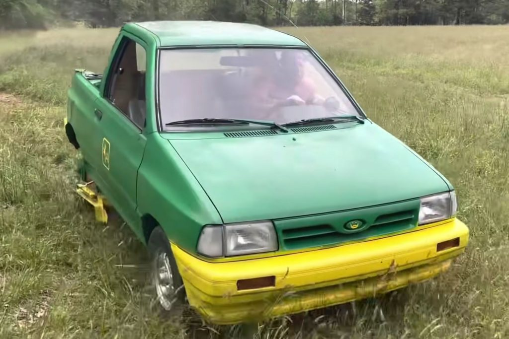 A green and yellow Ford Festiva compact car modified into a lawnmower