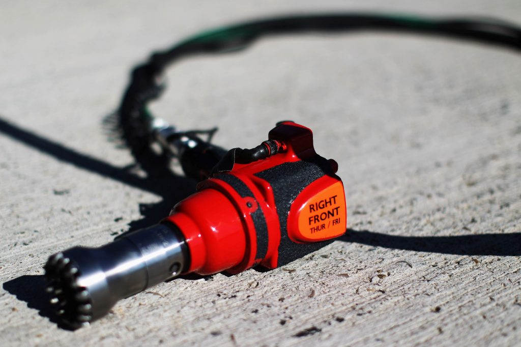 A red-black-and-orange Formula 1 wheel nut gun laying on the ground