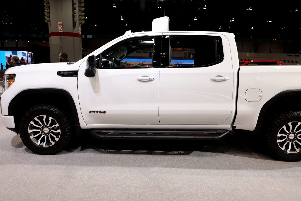 A white GMC Sierra parked in a showroom.