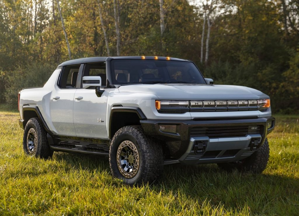 A white GMC Hummer EV Truck in a forest-lined grassy field