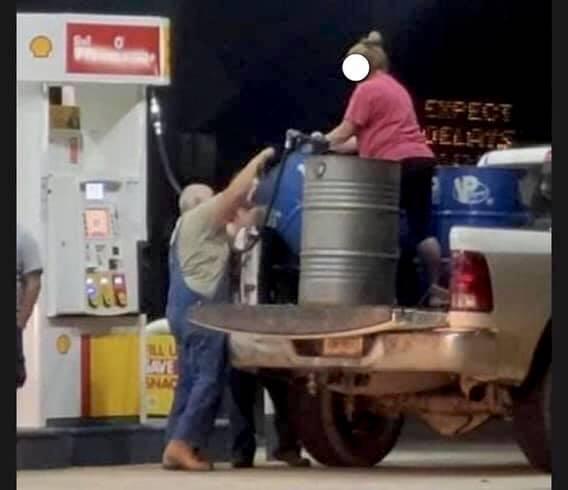 filling up oil barrels with gasoline