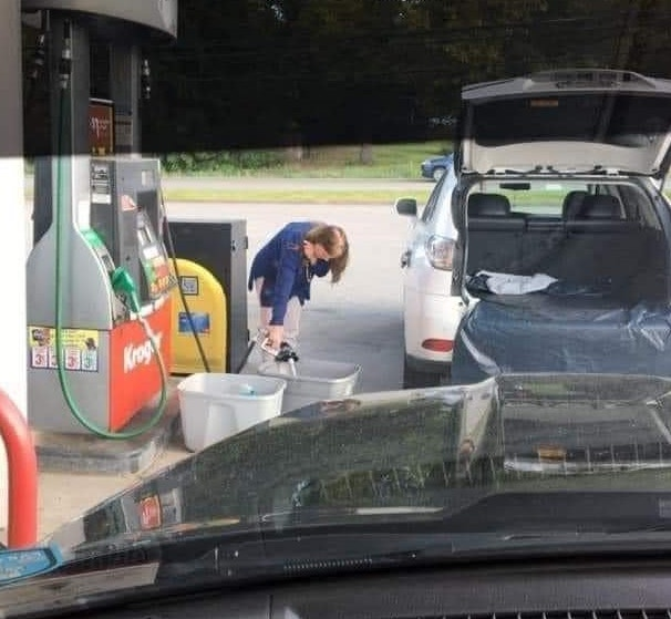 woman fills up plastic storage container with gas